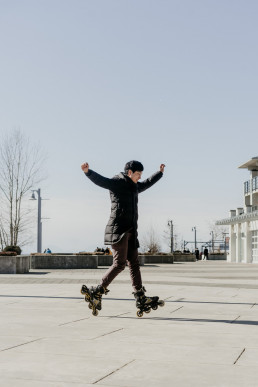 A man on rollerblades with his hands in the air.